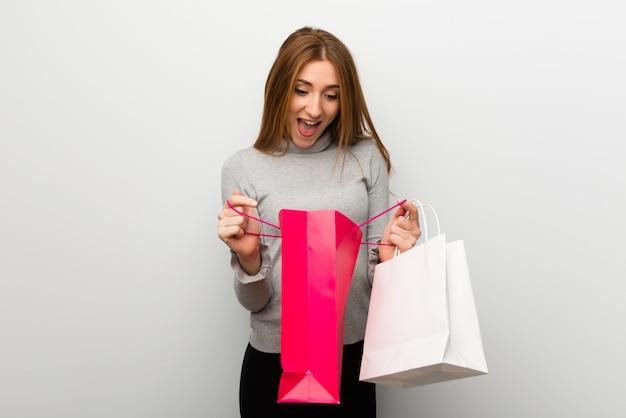 Ruda dziewczyna nad białą ścianą zaskoczona, trzymając wiele toreb na zakupy