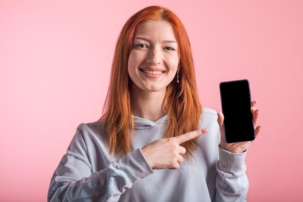 Ruda dziewczyna nastolatka wskazuje palcem na pusty ekran smartfona w studio na różowym tle