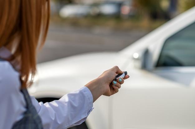 Ruda dziewczyna odblokowuje samochód za pomocą klucza bezprzewodowego
