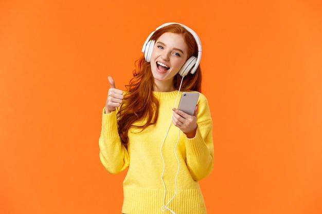 Ruda dziewczyna otrzymuje prezent na boże narodzenie nowe fajne słuchawki, słucha muzyki w słuchawkach i pokazuje kciuk, trzyma smartfona