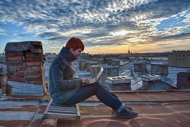 Ruda dziewczyna siedzi na dachu i pracuje z laptopem