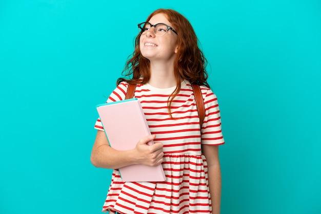 Ruda dziewczyna studentka nastolatka na białym tle na niebieskim tle myśląca o pomyśle, patrząc w górę