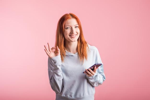 Ruda dziewczyna trzyma telefon i pokazuje ok gest w studio na różowym tle