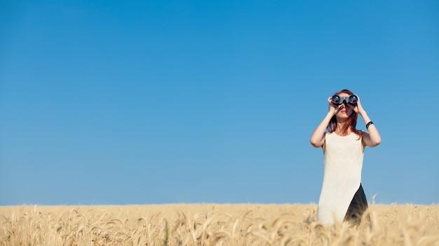 Ruda dziewczyna w białej sukni z lornetką na polu pszenicy.