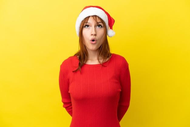 Ruda dziewczyna w bożonarodzeniowym kapeluszu na żółtym tle, patrząc w górę i ze zdziwionym wyrazem twarzy