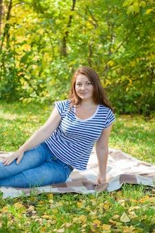 Ruda dziewczyna w parku. piknik na jesienne liście