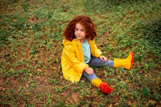 Ruda dziewczyna w płaszczu siedzi na trawiastej ziemi