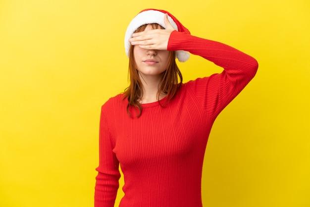 Ruda dziewczyna w świątecznym kapeluszu na białym tle na żółtym tle zasłaniając oczy rękami. nie chcę czegoś widzieć