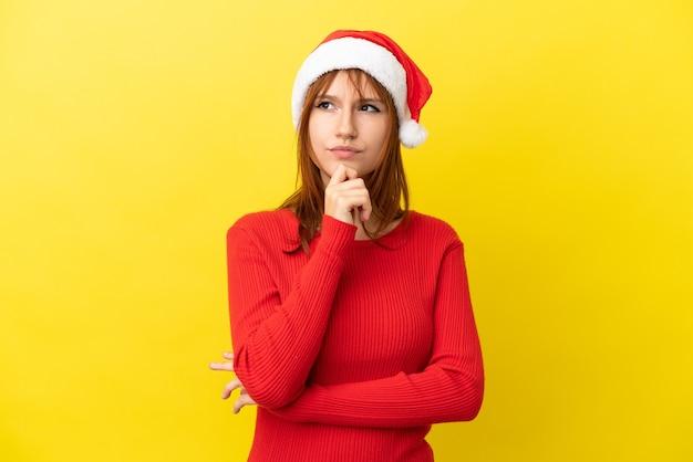 Ruda dziewczyna w świątecznym kapeluszu na żółtym tle i patrząc w górę