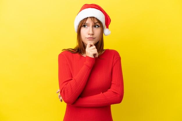 Ruda dziewczyna w świątecznym kapeluszu na żółtym tle ma wątpliwości i myśli