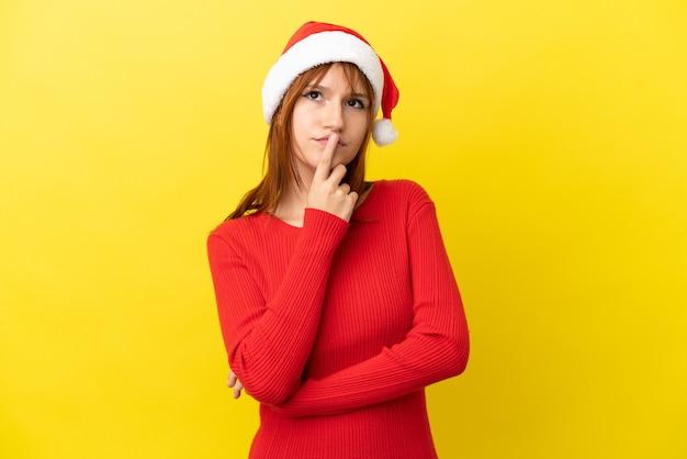 Ruda dziewczyna w świątecznym kapeluszu na żółtym tle ma wątpliwości podczas patrzenia w górę