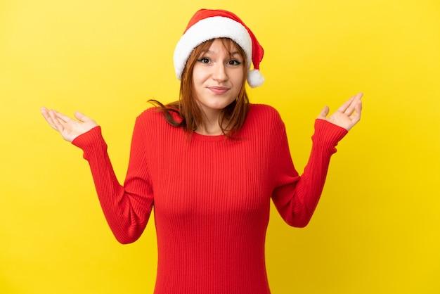Ruda dziewczyna w świątecznym kapeluszu na żółtym tle ma wątpliwości podczas podnoszenia rąk