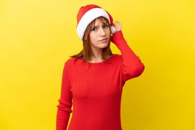 Ruda dziewczyna w świątecznym kapeluszu na żółtym tle ma wątpliwości