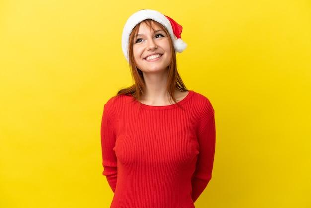 Ruda dziewczyna w świątecznym kapeluszu na żółtym tle myśląca o pomyśle, patrząc w górę