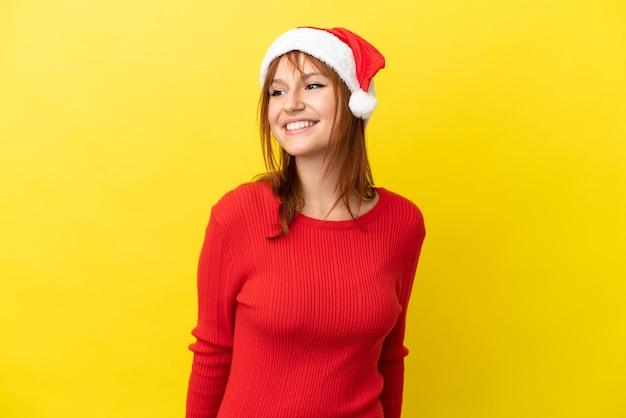 Ruda dziewczyna w świątecznym kapeluszu na żółtym tle, patrząc w bok i uśmiechnięta