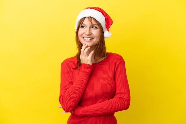Ruda dziewczyna w świątecznym kapeluszu na żółtym tle patrząc w górę podczas uśmiechu