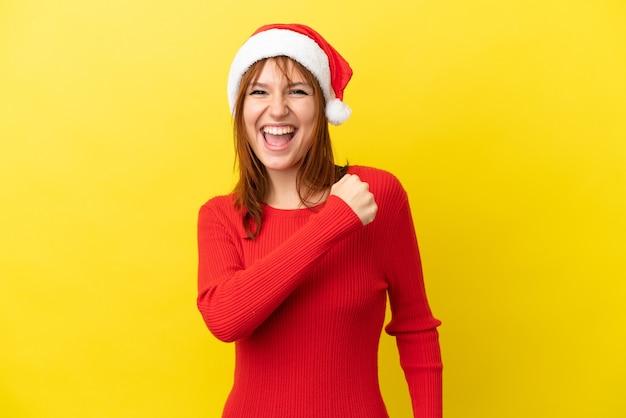 Ruda dziewczyna w świątecznym kapeluszu na żółtym tle świętuje zwycięstwo