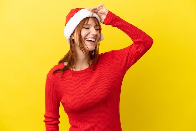Ruda dziewczyna w świątecznym kapeluszu na żółtym tle uśmiecha się dużo
