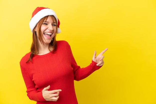 Ruda dziewczyna w świątecznym kapeluszu na żółtym tle, wskazując palcem na bok i prezentująca produkt