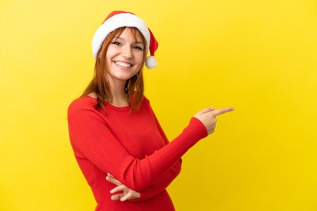 Ruda dziewczyna w świątecznym kapeluszu na żółtym tle, wskazując palcem w bok