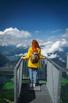 Ruda dziewczyna w żółtej kurtce patrzy na jezioro hallstatter hallstatt i okoliczne góry