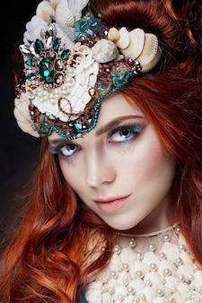 Ruda dziewczyna z jasnym makijażem i dużymi rzęsami. tajemnicza wróżka kobieta z rudymi włosami. duże oczy i kolorowe cienie, długie rzęsy. seksowny wygląd, czysta pielęgnacja skóry, pielęgnacja twarzy