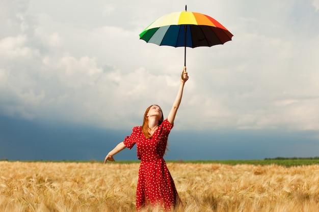 Ruda dziewczyna z parasolem w polu