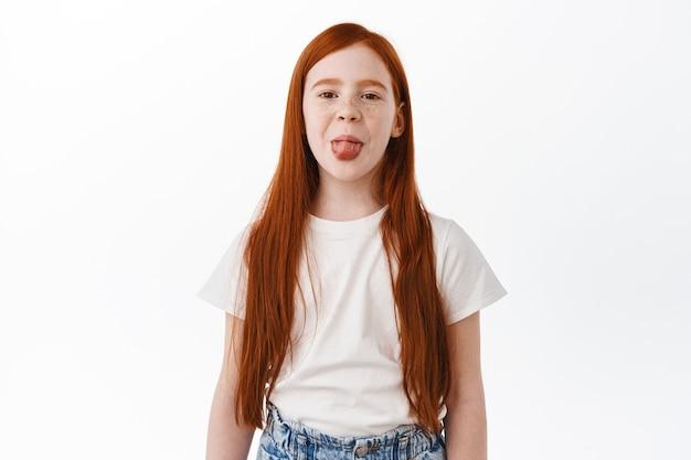 Ruda dziewczynka z długimi naturalnymi rudymi włosami i piegami, pokazuje język głupio i dziecinnie, bawiąc się. szczęśliwe dziecko z rudą fryzurą czuje się pozytywnie, biała ściana