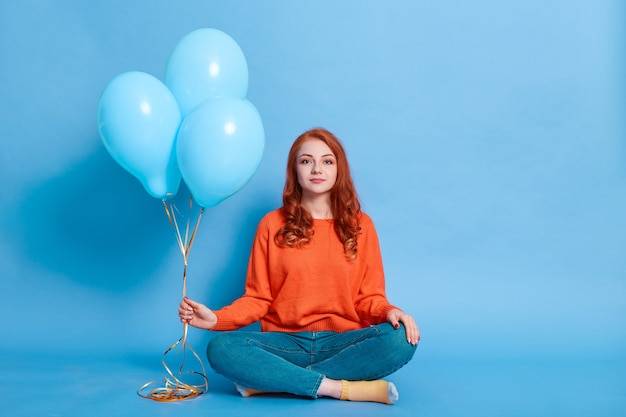Ruda europejka ubrana w pomarańczowy sweter i dżinsy trzyma balony w dłoniach siedząc na podłodze ze skrzyżowanymi nogami, rudowłosa dama ma urodziny, pozuje na niebieskiej ścianie.