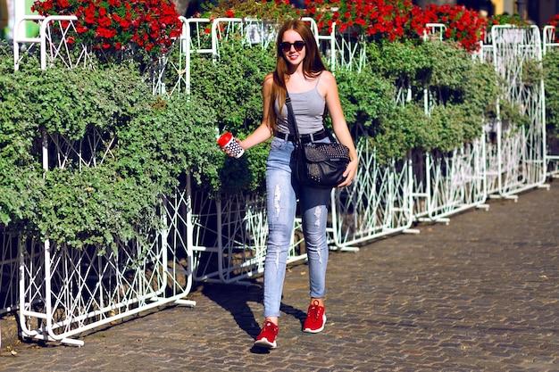 Ruda hipsterka dziewczyna spędza niesamowity słoneczny dzień na świeżym powietrzu, podróżuje po europie, swobodny styl hipster, pije smaczną kawę latte na wynos, ciesz się wakacjami i zrelaksuj się.