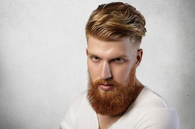 Ruda hipsterka z modną fryzurą i rozmytą brodą ubrana w białą koszulkę pozuje w pomieszczeniu, ma poważny i ponury wygląd.