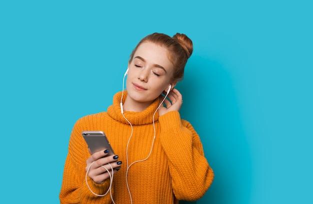 Ruda kaukaska kobieta z piegami słucha wesoło rozmyślań za pomocą telefonu i słuchawek, pozując na niebieskiej ścianie z wolną przestrzenią