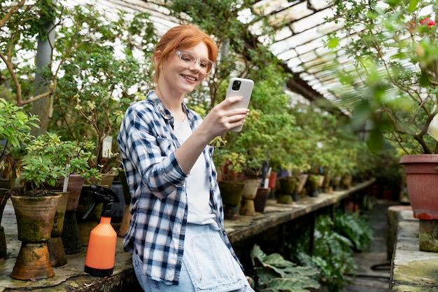 Ruda kobieta dbająca o swoje rośliny w szklarni