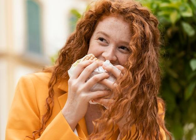 Ruda kobieta jedzenie ulicznego jedzenia