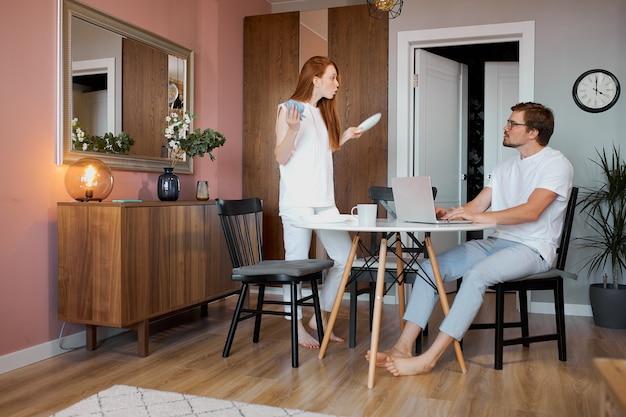 Ruda kobieta kłóci się z pracującym mężczyzną w domu