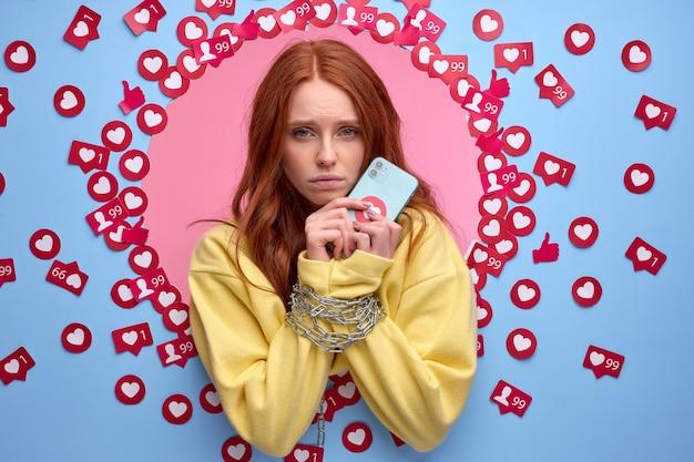 Ruda kobieta ma obsesję na punkcie internetu. kobiece ręce związane łańcuchem stojącym wśród lajków na niebieskiej ścianie