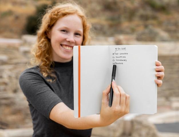 Ruda kobieta pokazuje dziennik