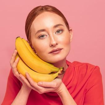 Ruda kobieta pozuje obok bananów