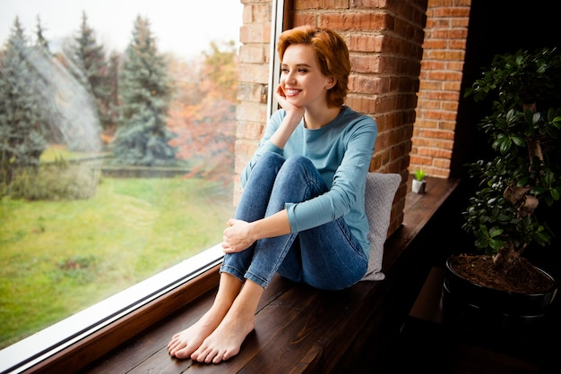 Ruda kobieta pozuje w pobliżu okna w domu