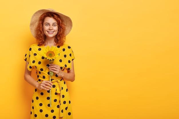 Ruda kobieta pozuje w żółtej sukience polka i słomkowym kapeluszu