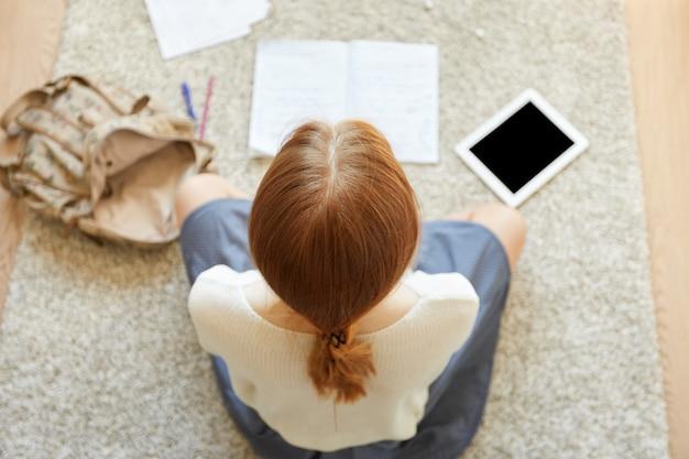 Ruda kobieta siedzi na podłodze z notatnikiem i tabletem