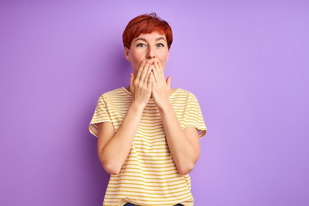 Ruda kobieta stoi z zamkniętymi ustami w szoku. odizolowane na fioletowej ścianie