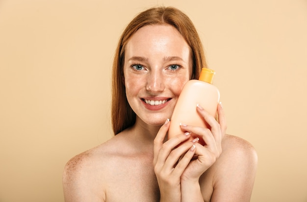 Ruda kobieta trzyma krem do pielęgnacji skóry.
