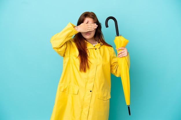 Ruda kobieta trzyma parasol na białym tle na niebieskim tle zasłaniając oczy rękami. nie chcę czegoś widzieć