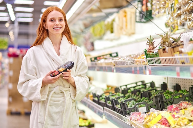 Ruda kobieta trzyma w rękach zapakowane warzywa, ubrana w szlafrok. w supermarkecie