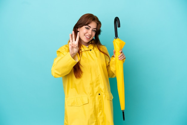 Ruda kobieta trzymająca parasol na białym tle na niebieskim tle szczęśliwa i licząca trzy palcami