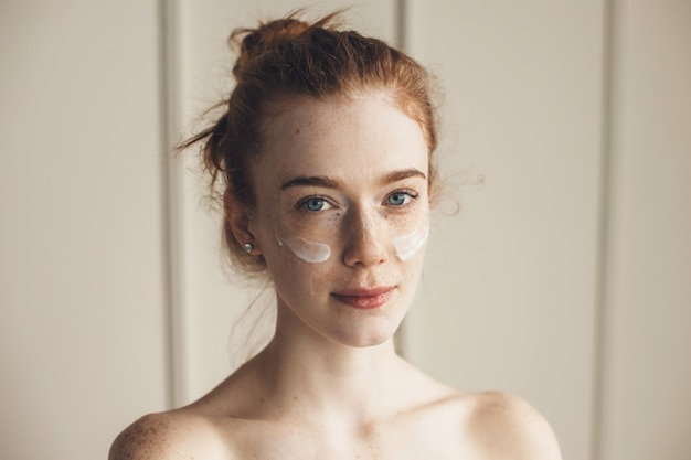 Ruda kobieta ubrana w hydrożelowe opaski na oczy patrząc na kamery z odkrytymi ramionami