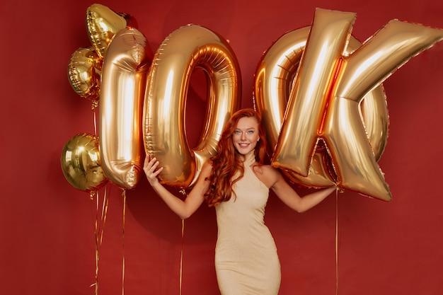 Ruda kobieta w eleganckiej sukni pozowanie podekscytowany trzymając złote balony na czerwono