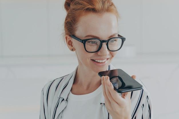 Ruda kobieta w przezroczystych okularach rozmawia z wirtualnym asystentem trzyma telefon komórkowy w pobliżu ust