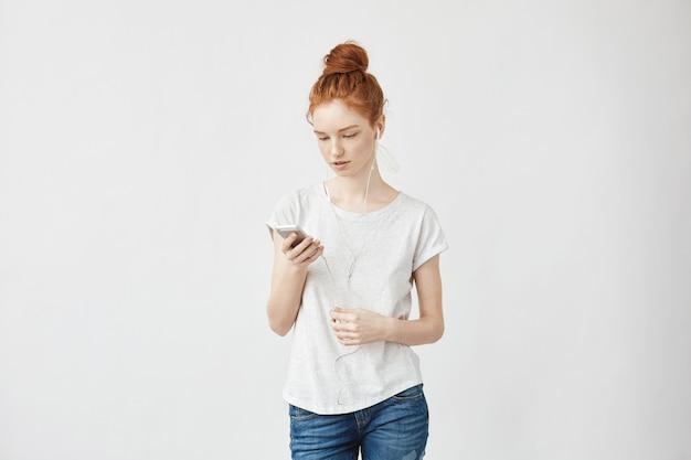 Ruda kobieta w słuchawkach, patrząc na telefon.
